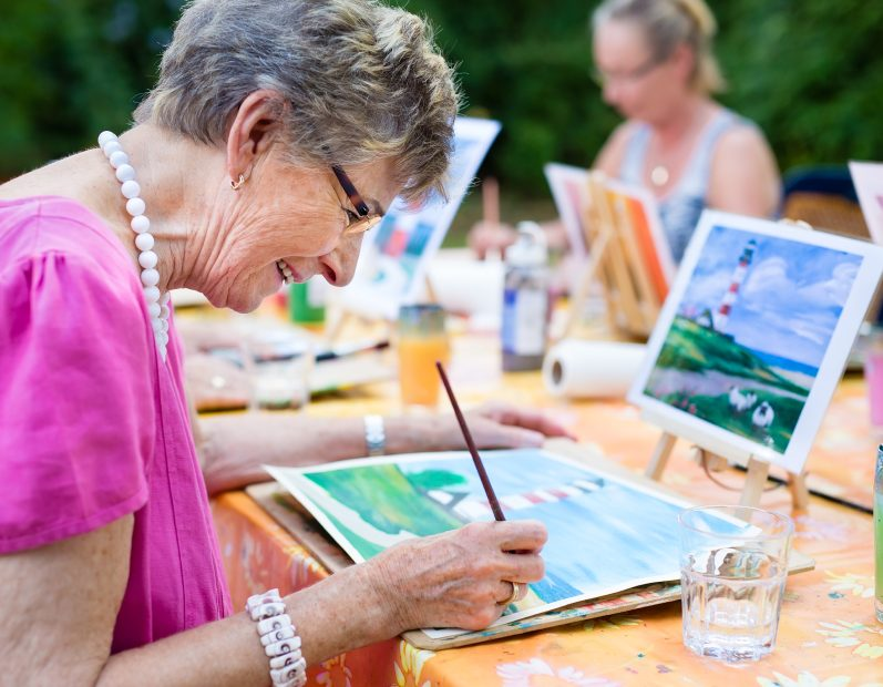 senior woman creating a painting of a lighthouse with watercolors