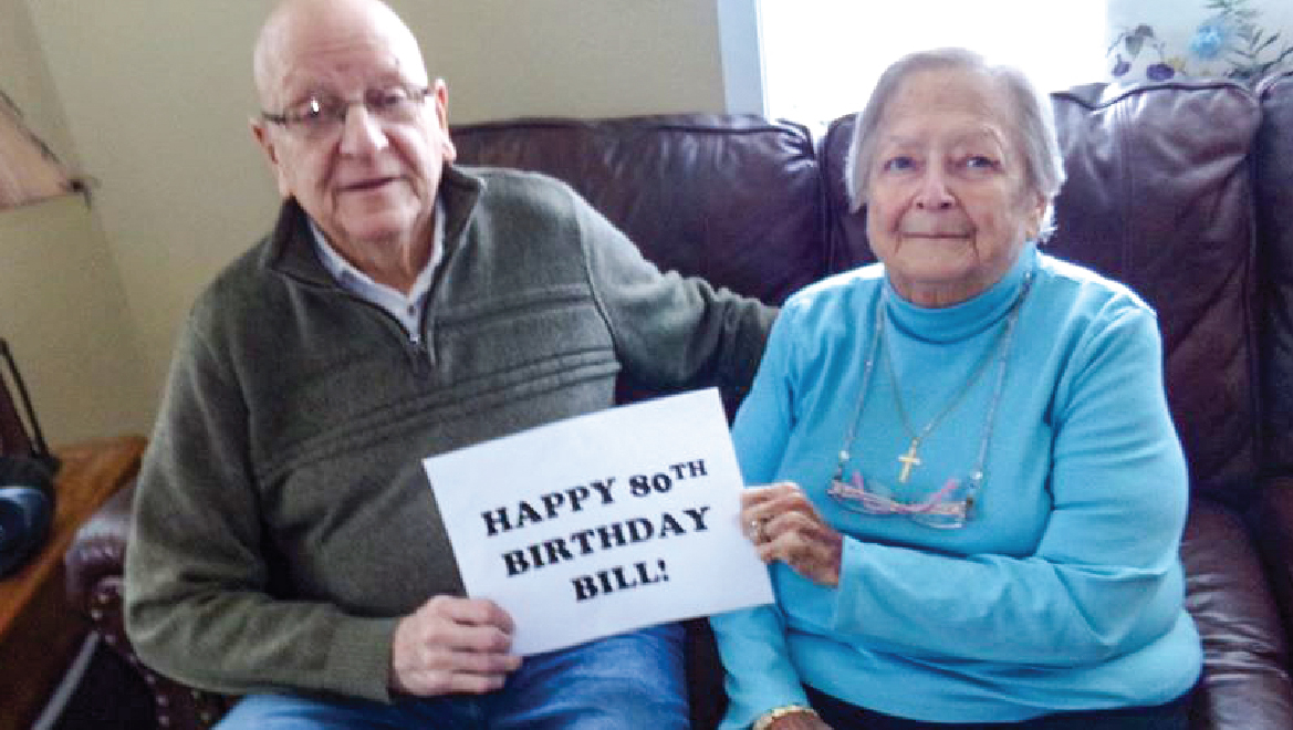 Senior couple holding a birthday message