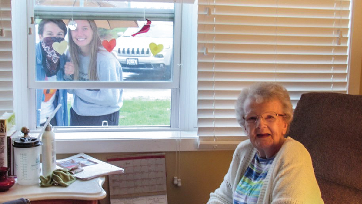 Female resident visiting with grandchildren through her window